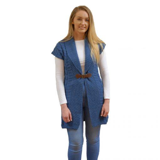 long sleeveless coat in aran knit pattern with buckle detail. Soft denim blue