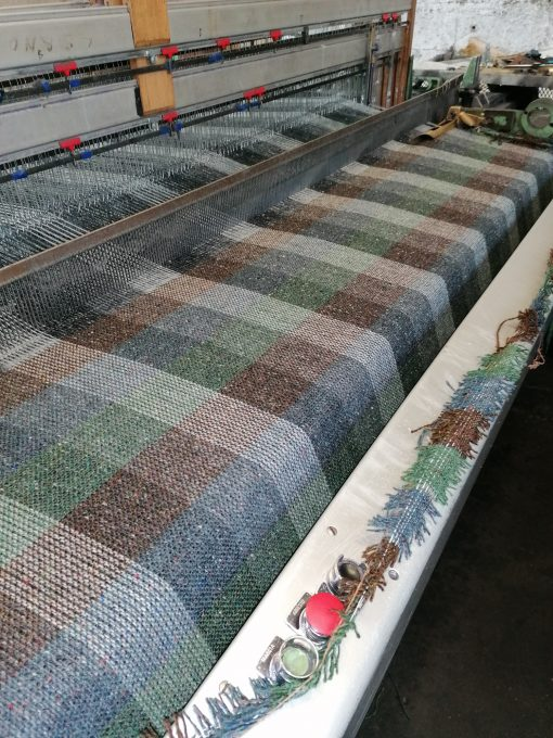 shows fabric on loom being woven at our mill