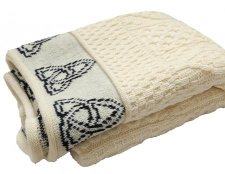 aran knit blanket in natural white with black trinity knot border .